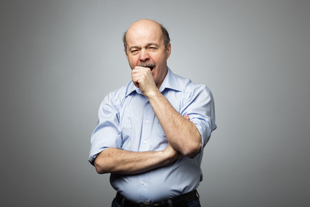 sleepiness: Bald man covers mouth with fist, yawning with fatigue and sleepiness. Tired of the work and desire to sleep