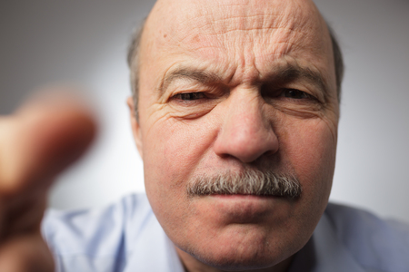 frowns: Elderly man dissatisfied frowns and looks sullenly. Poking his finger ahead Stock Photo