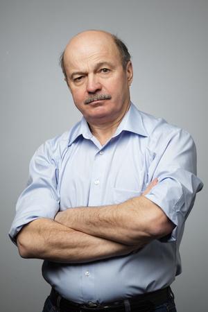 Portret van een senior man met gekruiste handen. Hij is boos Stockfoto