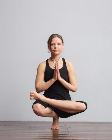 aum: Girl making one foot balance yoga pose. On the pendant is written yogic symbol Aum Stock Photo