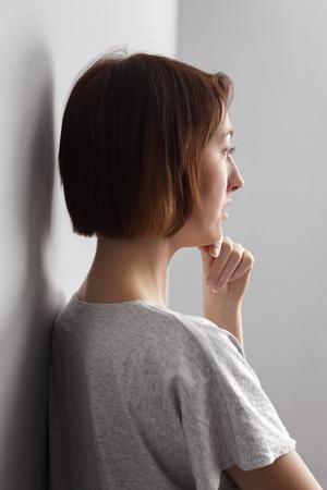 sadly: Girl sadly looks away, stroking his chin Stock Photo