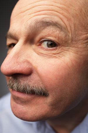 curiously: old man with a mustache looks curiously