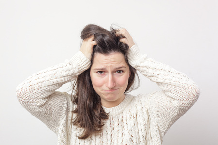 Girl in a white sweater desperately grabs her head because of stress and problems