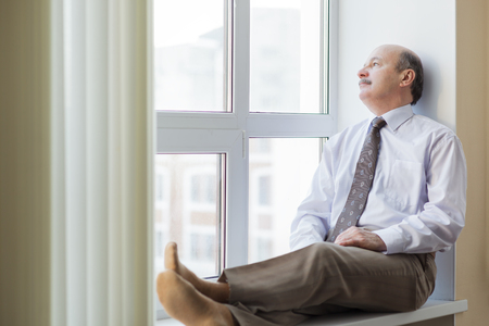 man in a shirt and tie sitting on a windowsill and dreamily looks out the window. Break during the working day. Stock Photo