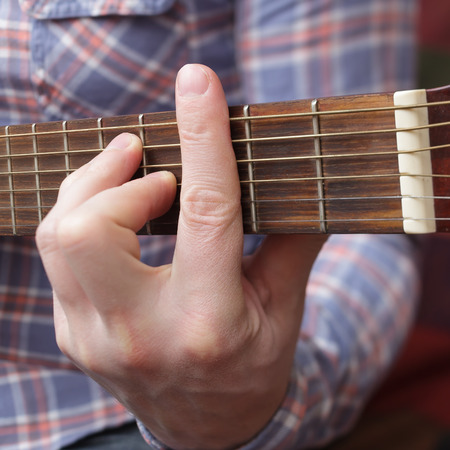 Young musician sets up a small guitar. Debugging musical instruments Stock Photo