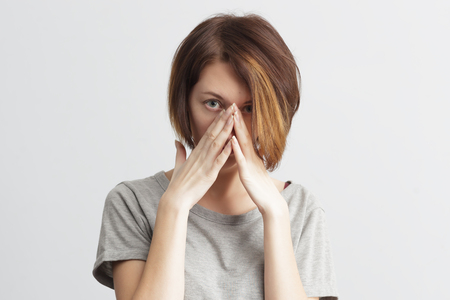 premenstrual syndrome: girl suffers from terrible headaches and compresses the head with fingers. Forget and remember something, suffer from illness Stock Photo