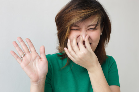 Japanese girl closes the nose with her hands. Unpleasant smell or stink