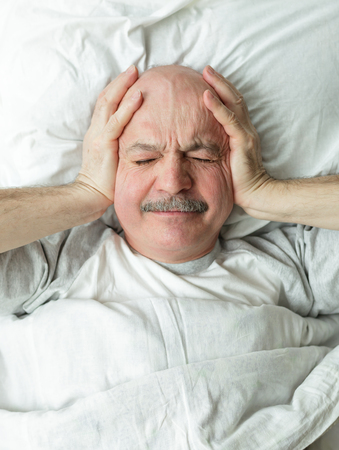 reluctance: An elderly man with a mustache does not want to get up in the morning, he wrinkles his face, closing his eyes from the bright light