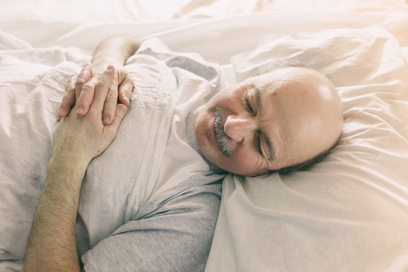 An elderly man lies on a bed and closes his eyes because of bright morning light