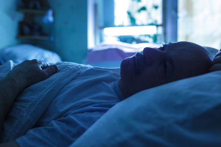 An elderly man suffers from insomnia, trying to sleep. Backlight image in blue tones.