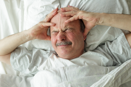 gente durmiendo: An elderly man can not fall asleep from loud noise and headaches. He holds his hands at the head, closes his ears with his fingers and frowns.