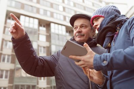 Een jong meisje met een tablet in haar handen vraagt ??voor een routebeschrijving van een vreemde. Hij toont haar met de vinger de juiste richting Stockfoto - 74505267