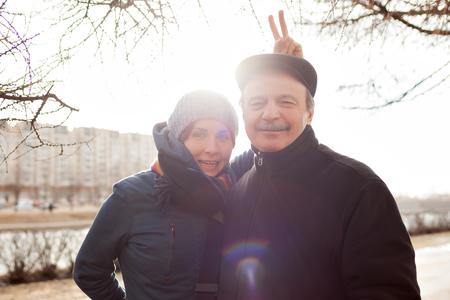 Familienportrait auf der Straße. Die Tochter setzt Hasenohren Papa Standard-Bild