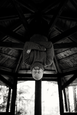 A brutal man in a sweater hangs upside down on the crossbar. He crossed his arms over his chest, his eyes closed. Rest in an uncomfortable position. Stylization for black and white film