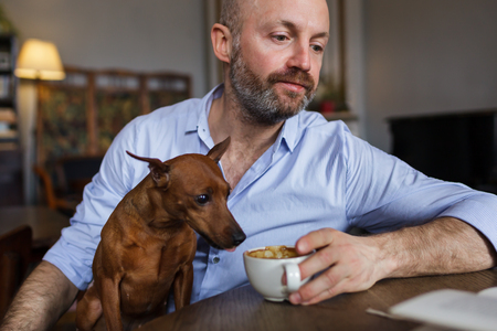 attempt: The man is resting with his dog. He reads the book, and the dog discreetly tastes coffee from his cup