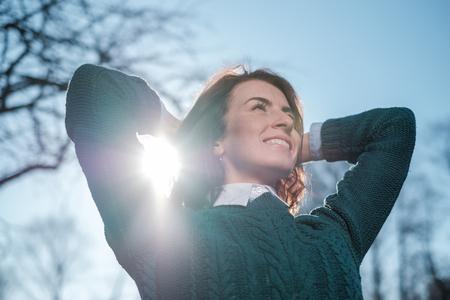 赤い髪の少女の笑顔、太陽の光を楽しみます。彼女は彼女の頭の後ろに彼女の腕を交差しました。散歩に肯定的な気分
