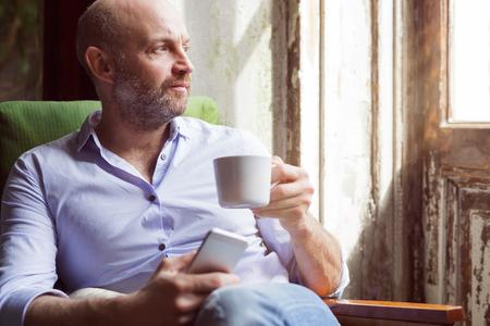 Een man drinkt koffie en controleert het nieuws in de telefoon, zittend in een stoel bij het raam