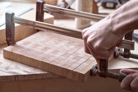fastens: Joiner fastens clamps on a wooden surface for better gluing. Joinery work on the creation of furniture