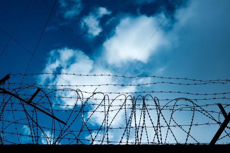 Barbed wire around the perimeter of a prison or a secret facility
