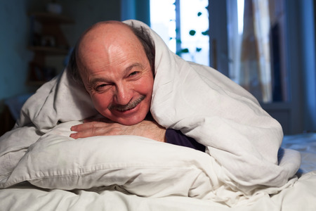 An elderly bald man with a mustache lies in bed, hugging a pillow. He has a problem with sleep.