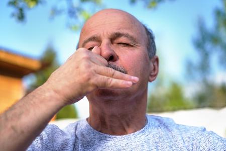 prana: Handsome mature man breathing yoga pranayama on summer sunny day outside.