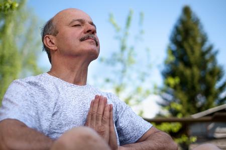 Yoga in het park. Senior man met snor met namaste vergadering. Concept van rust en meditatie. Stockfoto