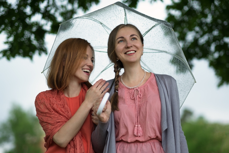 rumour: Two women walking park in rain and talk. Friendship and people communication.