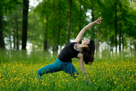 Young woman doing yoga on a green forest.