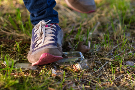 Woman goes on the grass in sneakers. Risk of stepping on a splinter of broken bottle glass.