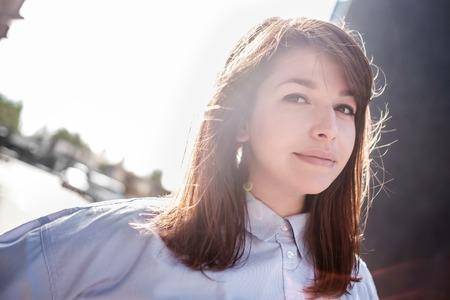 Mooi vrouwenportret buitenshuis met achterlicht. Stockfoto