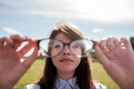 Young beautiful girl in shirt with long hair looks through glasses.
