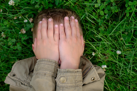 blind child: Teenage boy closes his eyes with hands Stock Photo