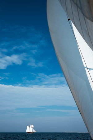 ocean waves: White sail yacht against the blue sky and the sea.