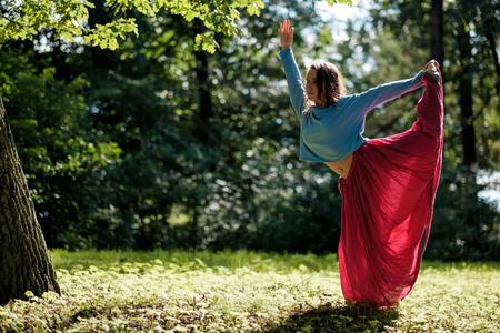 Sporty fit caucasian woman doing asana Virabhadrasana 2 Warrior pose posture in nature. Stock Photo