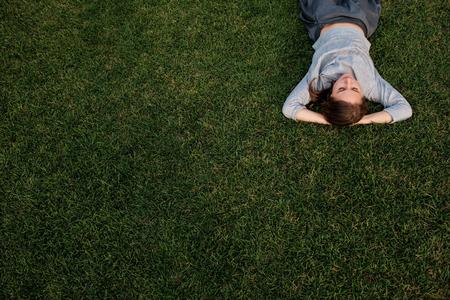 De mooie jonge Europese vrouw bepaalt op gras en rust Stockfoto