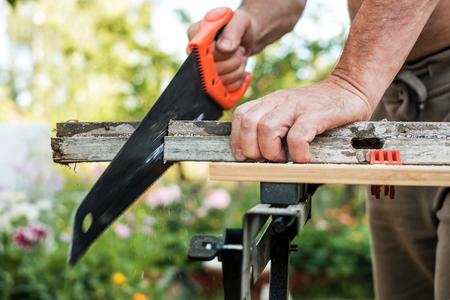 Kaukasischer Mann, der Planke mit Handsaw im Freien im Sommer bearbeitet.