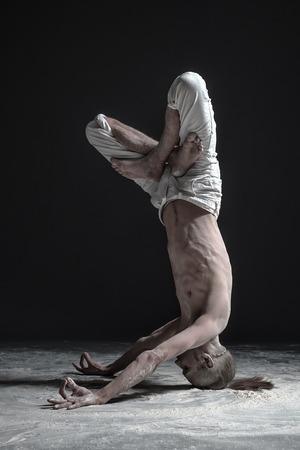 Flexible yoga man standing in yoga shirshasana headstand pose.