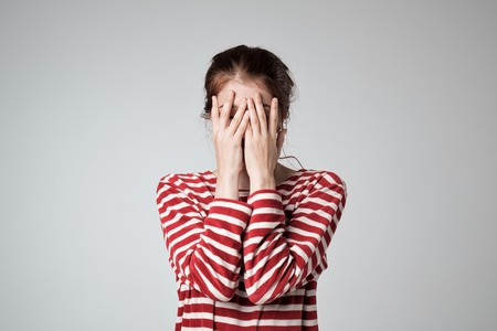 Pretty caucasian girl covers her face with her hands Stock Photo