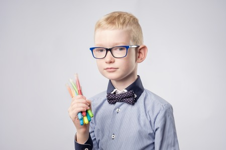 Caucasian boy with blond hair holding pencils in hands and looking up Stock Photo