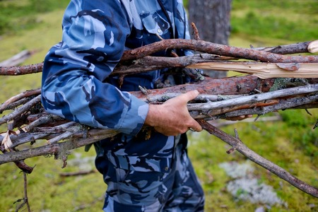 compile: The man is carrying an armful of brushwood in his hands. Preparations for kindling a fire.