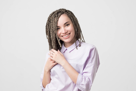 Woman smiling with perfect smile and white teeth. Her hair made in african braids. Confident facial expression