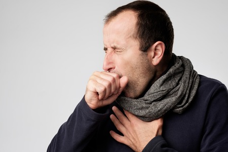 Mature man in scarf is ill from colds or pneumonia. Suffering from flu virus. Stock Photo