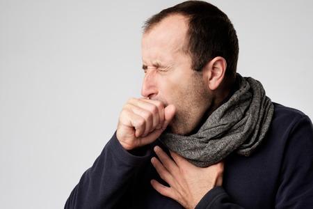 Oudere man in sjaal is ziek van verkoudheid of longontsteking. Lijden van griepvirus.