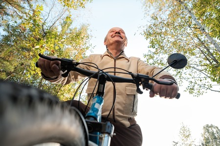 Senior caucasian man on cycle ride in countryside. Green trees on background. He is happy and active. Stock Photo