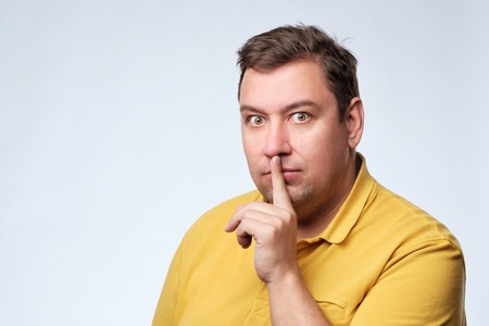 Finger on lips as man gesturing shh sign. Fat caucasian guy ask to be silent