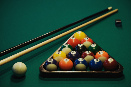 Playing billiard. Billiards balls and cue on green billiards table. Billiard sport concept. Pool billiard game. Stock Photo