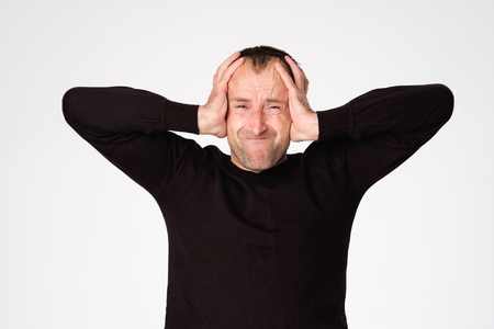 Mature spanish man closing his ears because of headache or migraine. Concept of loud sound and neurosis 版權商用圖片