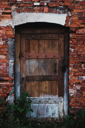 Old wooden door in a red face brick building. Close up view of architectural decay