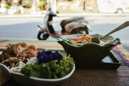 Two plates of spicy Thai food on the veranda on the street. In the background motorcycle. Snack while traveling and resting. Reklamní fotografie