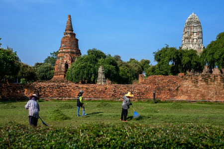 AYUTTHAYA, THAILAND - OCTOBER 31, 2017: Wat Phra Si Sanphet temple in Ayutthaya Historical Park. Workers clean the territory of the park and mow the grass